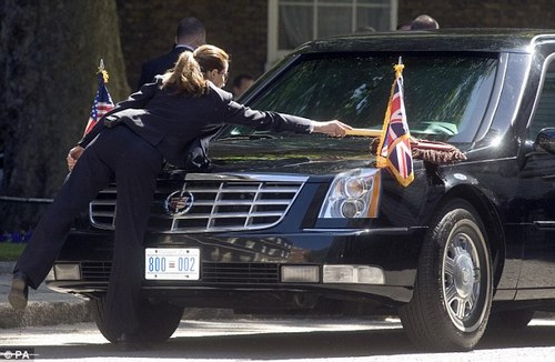 The smartly dressed driver of the President's vehicle  brushes down its shiny exterior as she waits for him outside the Prime  Minister's residence